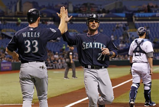 Seattle Mariners' Casper Wells, left, and John Jaso celebrate after scoring on a single by Michael Saunders as Tampa Bay Rays catcher Jose Lobaton looks on during the first inning of a baseball game Saturday, July 21, 2012, in St. Petersburg, Fla. (AP Photo/Mike Carlson)