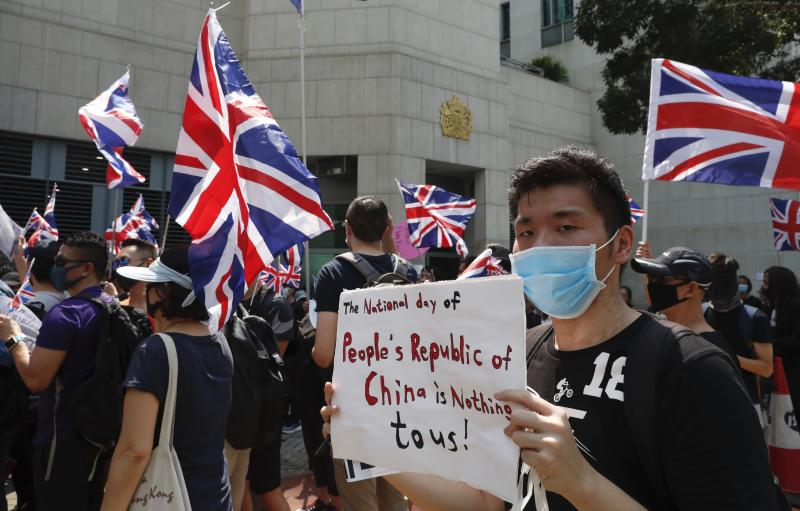 A man holds a placard as a group of Hong Kong residents waving U.K. flags demonstrate requesting right to British residency, Tuesday, Oct. 1, 2019, outside the British embassy in Hong Kong while the celebration of the People's Republic's 70th anniversary is taking place in Beijing. Police used pepper spray to break up a brief scuffle Tuesday between Beijing supporters and a small group of pro-democracy protesters who were marching in Hong Kong on the 70th anniversary of the founding of Communist China. (AP Photo/Gemunu Amarasinghe)