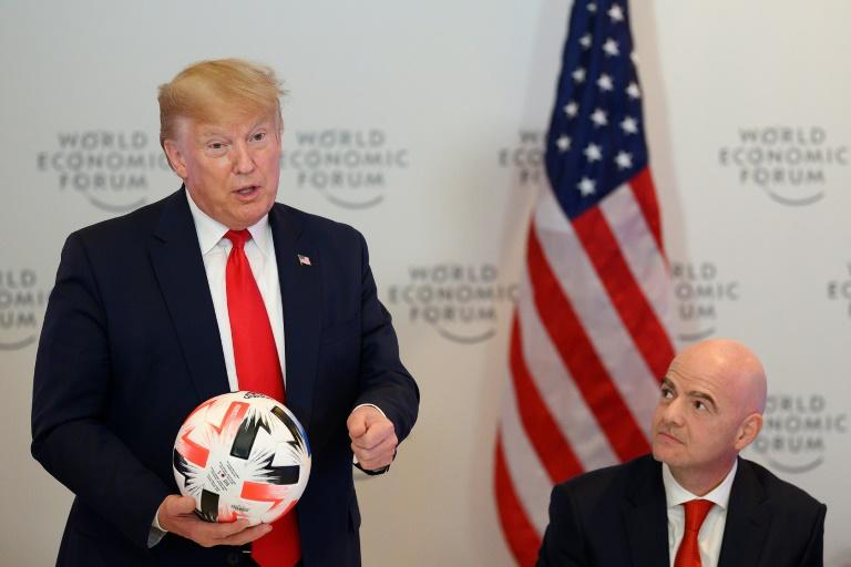 US President Donald Trump go a football from FIFA President Gianni Infantino at the Davos forum