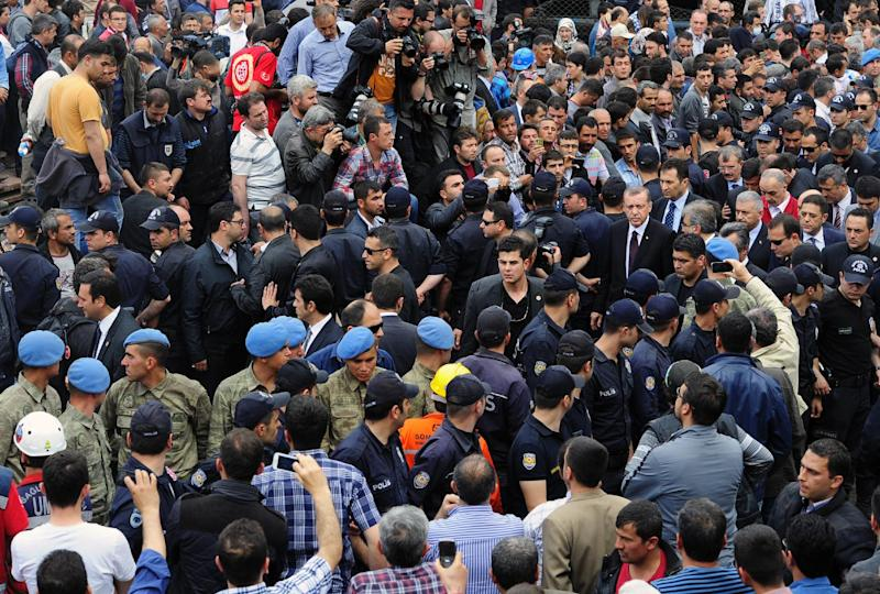Turkey's Prime Minister Recep Tayyip Erdogan, center right, is surrounded by security members as he visits the coal mine in Soma, Turkey, Wednesday, May 14, 2014. An explosion and fire at the coal mine killed at least 232 workers, authorities said, in one of the worst mining disasters in Turkish history. Turkey's Energy Minister Taner Yildiz said 787 people were inside the coal mine at the time of the accident. (AP Photo/Emre Tazegul)