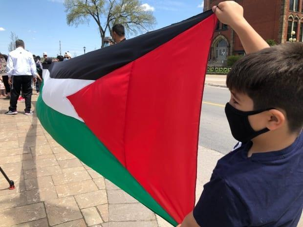 A young boy shows his support for the Palestinians at a rally in Fredericton on Sunday.