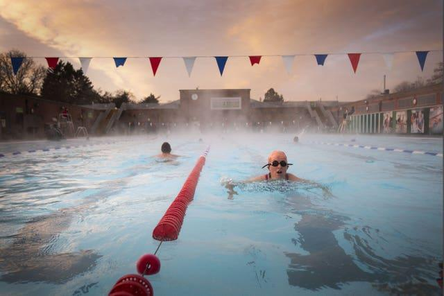 Early morning swimmers during sunrise at Charlton Lido in Hornfair