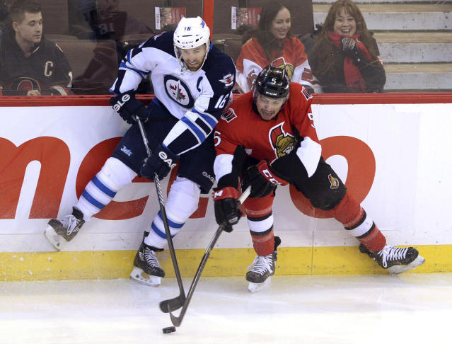 Ottawa Senators' Cody Ceci, right, and Winnipeg Jets' Adrew Ladd compete for the puck during the first period of an NHL hockey game in Ottawa, Ontario, on Thursday, Jan. 2, 2014. (AP Photo/The Canadian Press, Sean Kilpatrick)