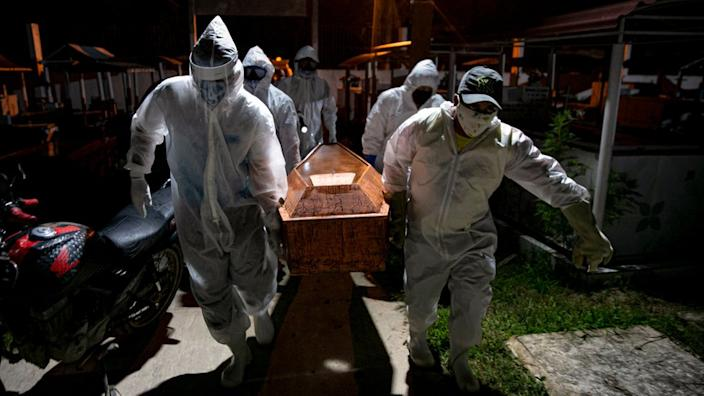 Gravediggers wearing protective clothing carry the coffin of a victim of the coronavirus