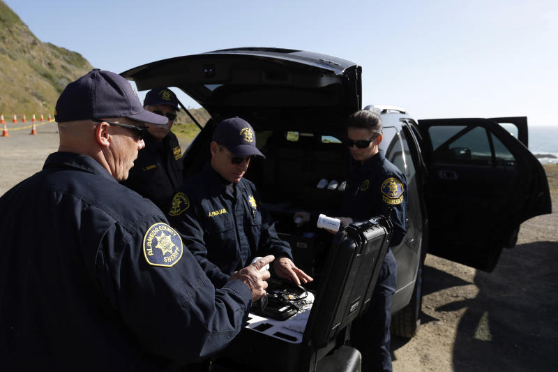 Members of the Alameda County Sheriff's Office drone team pack up their equipment after a search for three missing children Wednesday, March 28, 2018, at the site where the bodies of Jennifer and Sarah Hart and three of their adopted children were recovered two days earlier, after the family's SUV plunged over a cliff at a pullout on the Pacific Coast Highway near Westport, Calif. Three of the children, Devonte Hart, 15, Hannah Hart, 16, and Sierra Hart, 12, have not been found.