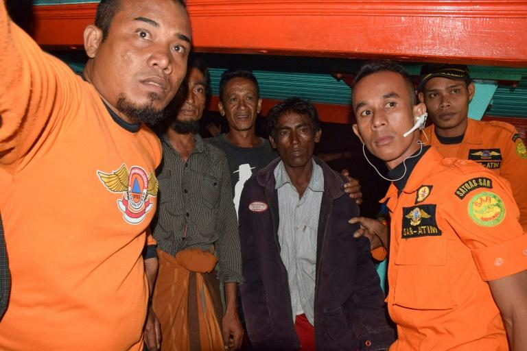 The Rohingya (flanked by rescuers) were taken to Aceh by Indonesian fishermen