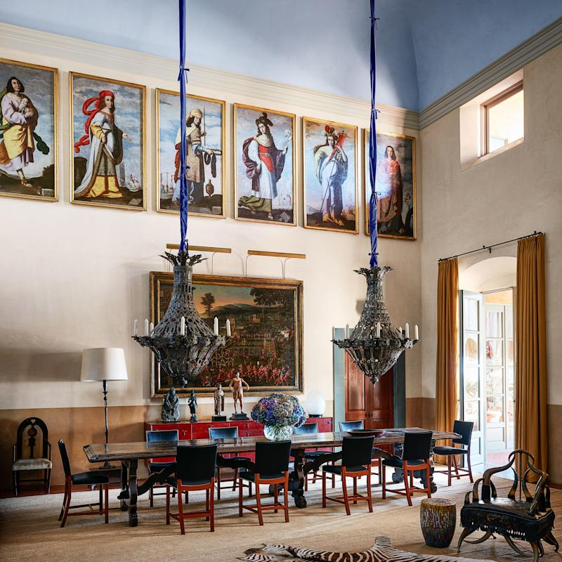 Renaissance-era paintings hang along the great-room cornices. The custom blue ombré ceiling evokes the sky; Mexican candelabras.