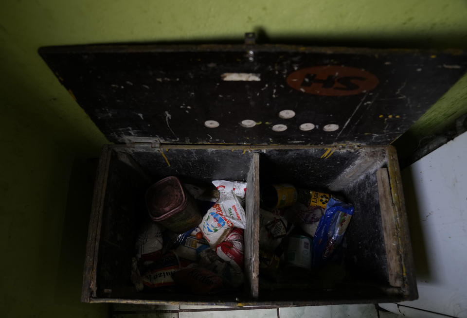 """The pantry of Lady Laurentino, 74, is shown almost empty at her home in the Jardim Gramacho favela of Rio de Janeiro, Brazil, Monday, Oct. 4, 2021. Laurentino who now cooks with firewood instead of gas because of the recent surge in prices, says that at night she hopes it doesn't rain. """"There is no other way, I use firewood. If, at night, I can heat up the food, but if it rains, I eat it cold."""" She says. (AP Photo/Silvia Izquierdo)"""