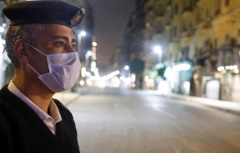 A police officer stands at the Qasr El Nil street during the first day of a two-weeks night-time curfew which was ordered by the Egyptian Prime Minister Mostafa Madbouly to contain the spread of the coronavirus disease (COVID-19), in Cairo