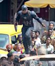Chris Evans, in full Cap gear, races through a crowd and over some cars during a chase scene. The Atlanta location has seemingly been transformed into an African street.