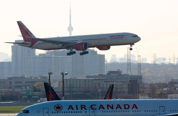 Air India flight 187 from New Delhi lands at Pearson airport in Toronto on Friday. The flight was the last landing allowed after all flights from India and Pakistan to Canada were suspended. (Frank Gunn/The Canadian Press - image credit)