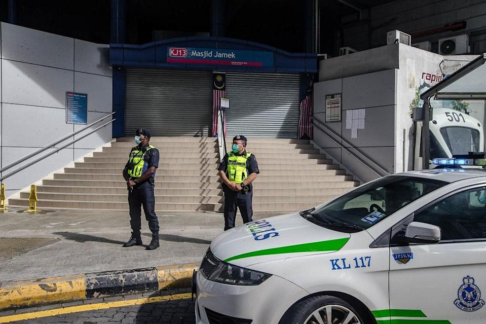 Police personnel stand guard outside the Masjid Jamek LRT station in Kuala Lumpur.