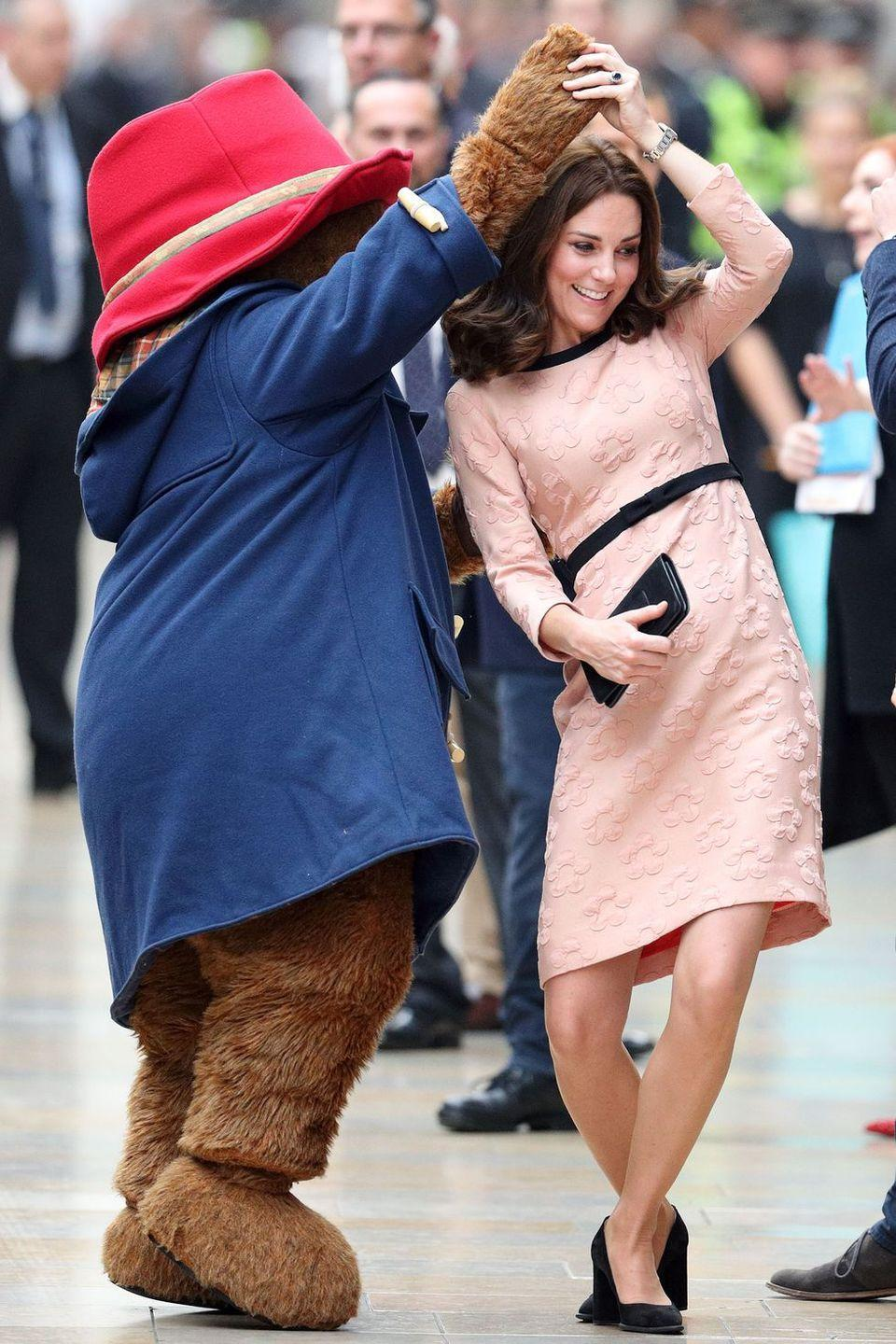 <p>Duchess Kate dances with Paddington Bear as she arrives at the Charities Forum Event at Paddington Station with Prince William.</p>