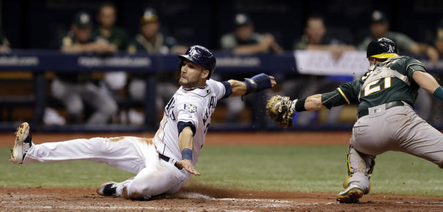 Tampa Bay Rays' Kevin Kiermaier, left, slides around a tag by Oakland Athletics catcher Jonathan Lucroy to score on a sacrifice fly by Jake Bauers during the sixth inning of a baseball game, Saturday, Sept. 15, 2018, in St. Petersburg, Fla. (AP Photo/Chris O'Meara)