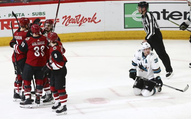 Arizona Coyotes defenseman Jakob Chychrun (6), defenseman Alex Goligoski (33), center Clayton Keller (9) and right wing Conor Garland (83) celebrate a goal by Alex Galchenyuk, while San Jose Sharks center Logan Couture (39) kneels on the ice and linesman Mark Shewchyk (92) skates past during the third period of an NHL hockey game Wednesday, Jan. 16, 2019, in Glendale, Ariz. The Coyotes defeated the Sharks 6-3. (AP Photo/Ross D. Franklin)