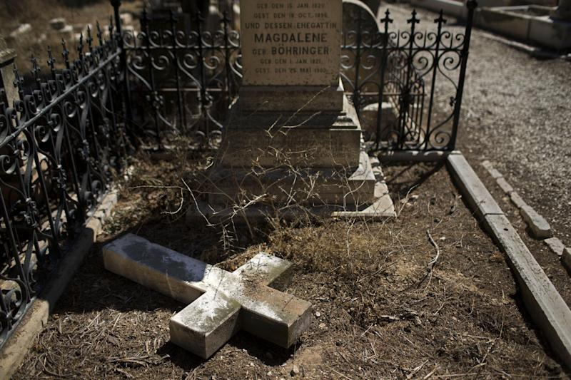 In this Monday, Oct. 7, 2013 photo, a damaged grave after a vandal attack is shown in the Protestant Cemetery of Mt. Zion, Jerusalem. Christian leaders in the Holy Land are up in arms over what they say is a string of relentless attacks on church properties and religious sites _ most recently the desecration of a historic Protestant cemetery where vandals toppled stone crosses from graves and bludgeoned them into pieces. (AP Photo/Bernat Armangue)