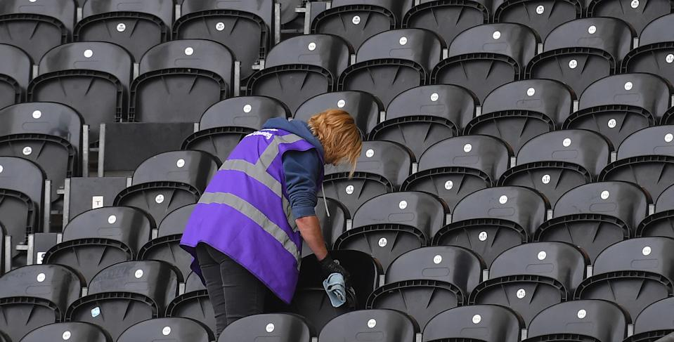 A cleaner cleans seats prior to a football game. Photo: Dave Howarth/EMPICS Sport
