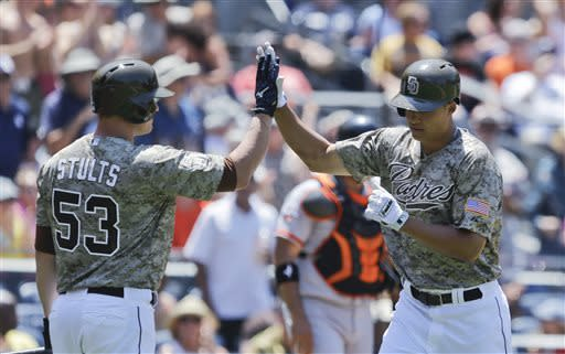 San Diego Padres' Will Venable, right, is congratulated by Eric Stults after his solo home run against the San Francisco Giants in the second inning of a baseball game in San Diego, Sunday, July 14, 2013. (AP Photo/Lenny Ignelzi)