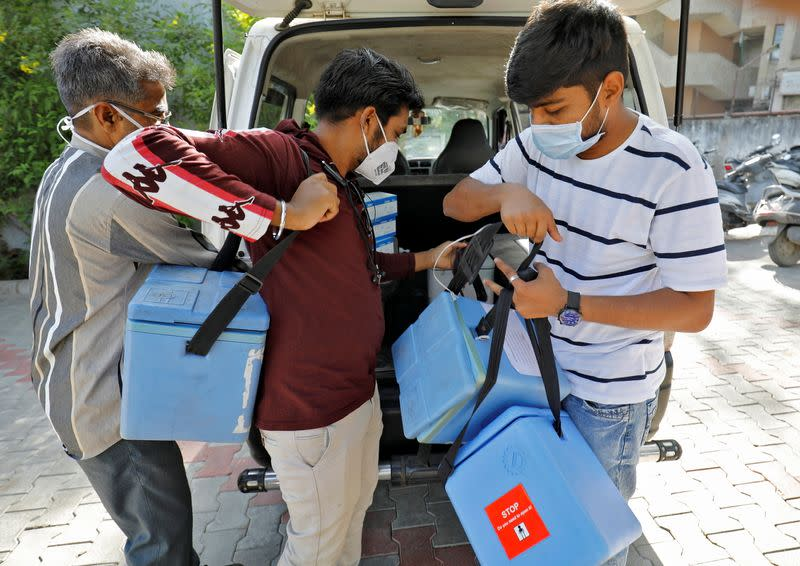 Healthcare workers unload boxes containing vials of COVISHIELD, a coronavirus disease (COVID-19) vaccine, in Ahmedabad