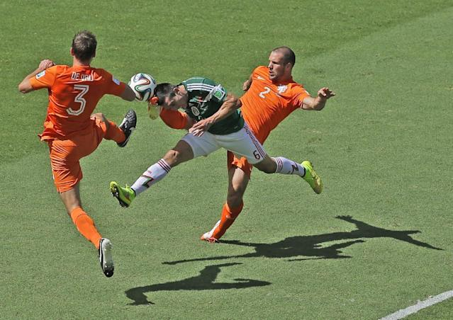 Mexico's Hector Herrera, center, challenges for the ball with Netherlands' Stefan de Vrij, left, and Ron Vlaar during the World Cup round of 16 soccer match between the Netherlands and Mexico at the Arena Castelao in Fortaleza, Brazil, Sunday, June 29, 2014. (AP Photo/Themba Hadebe)