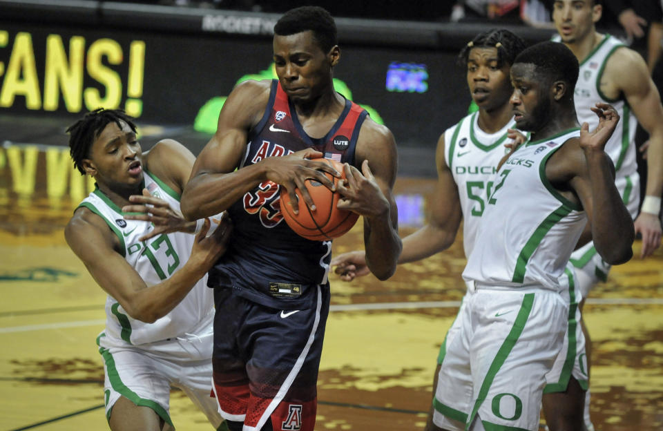 Arizona center Christian Koloko (35) secures the ball as he is defensed by Oregon forwards Chandler Lawson (13), Eric Williams Jr. (50) and Eugene Omoruyi (2) during the first half of an NCAA college basketball game Monday, March 1, 2021, in Eugene, Ore. (AP Photo/Andy Nelson)
