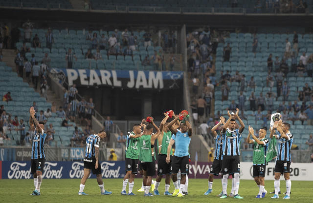 Players of Brazil's Gremio applaud at the end of a Copa Libertadores soccer match against Internacional at Gremio Arena in Porto Alegre, Brazil, Thursday, March 12, 2020. Match ended 0-0. (AP Photo/Liamara Polli)