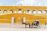 <p>As the ancient site for worshipping the Mayan sun god, Itzamná, it's only fitting for Izamal to explode with vivid yellow shades. Nearly every church, home, and shop along the cobblestone street is painted a sunny shade, but the reasoning remains unclear. It was thought that the city was painted yellow in honor of Pope John Paul II in 1993; however, many locals will tell you that the yellow shade starting appearing centuries before. At the town's grassy center remains a plethora of Mayan ruins to explore, including the Kinich Kakmó Pyramid.</p>