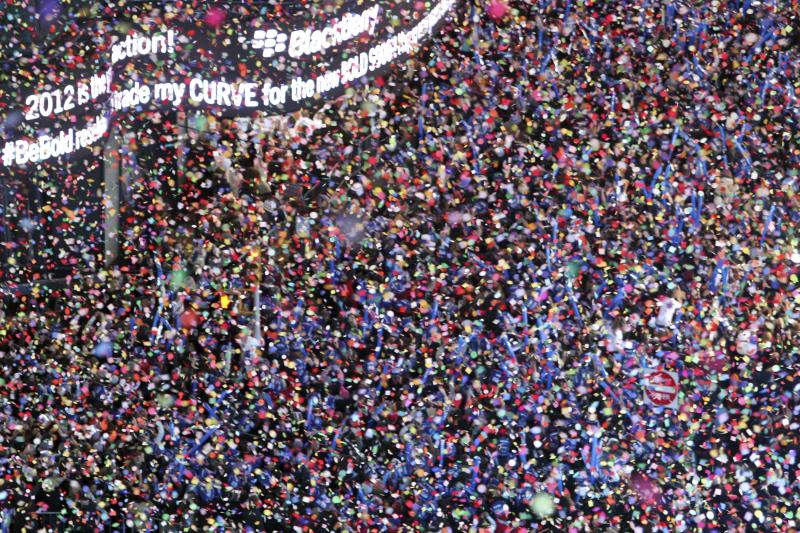 """FILE - In this Dec. 31, 2011 file photo, confetti flies over New York's Times Square as the clock strikes midnight during the New Year's Eve celebration as seen from the balcony of the Marriott Marquis hotel. It's no small task making sure the annual celebration remains safe, but the New York City police use an array of security measures for the event that turns the """"Crossroads of the World"""" into a massive street party in the heart of Manhattan. (AP Photo/Mary Altaffer, File)"""
