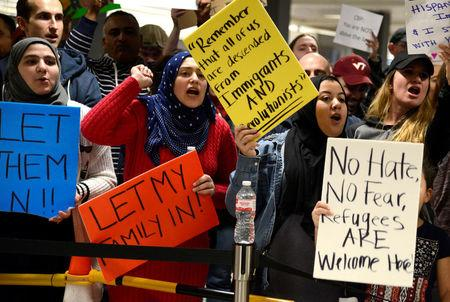 Dozens of pro-immigration demonstrators cheer and hold signs as international passengers arrive at Dulles International Airport in Chantilly, Virginia