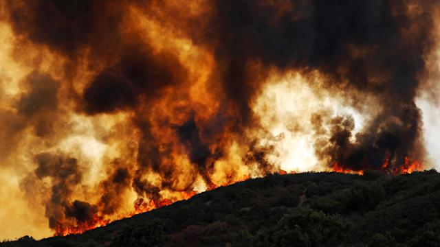 <p>Wind-driven flames roll over a hill towards homes during the River Fire (Mendocino Complex) near Lakeport, Calif., Aug. 2, 2018. (Photo: Fred Greaves/Reuters) </p>