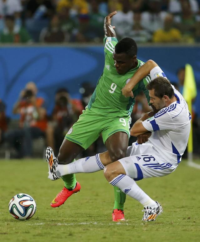 Bosnia's Senad Lulic (R) fights for the ball against Nigeria's Emmanuel Emenike during their 2014 World Cup Group F soccer match at the Pantanal arena in Cuiaba June 21, 2014. REUTERS/Eric Gaillard (BRAZIL - Tags: SOCCER SPORT WORLD CUP)