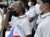 A masked city hall employee wipes sweat from his head during ceremonies in observance of National Flag Day outside Manila's city hall, Philippines on Thursday, May 28, 2020, as the capital observes community quarantine to avoid the spread of the new coronavirus. (AP Photo/Aaron Favila)