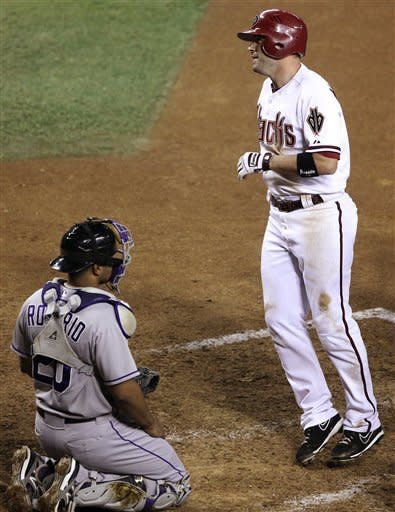 Arizona Diamondbacks' John McDonald, right, heads back to the dugout after hitting a two-run home run against the Colorado Rockies in front of Rockies catcher Wilin Rosario, left, in the seventh inning of a baseball game, Tuesday, Oct. 2, 2012, in Phoenix. (AP Photo/Paul Connors)