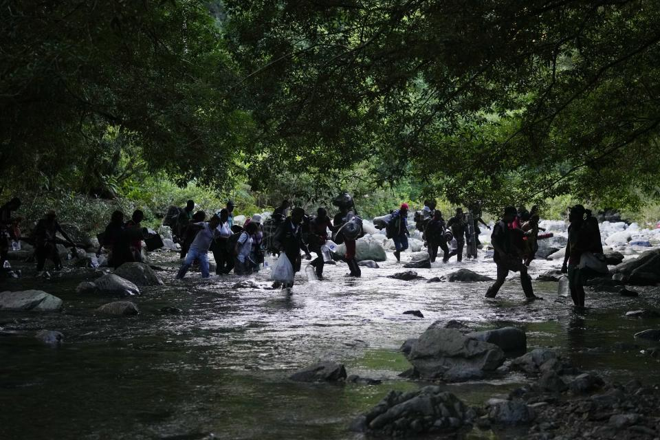 Migrants cross the Acandi River as they continue on their trek north, in Acandi, Colombia, Wednesday, Sept. 15, 2021. The migrants, following a well-beaten, multi-nation journey towards the U.S., will continue their journey through the jungle known as the Darien Gap. (AP Photo/Fernando Vergara)