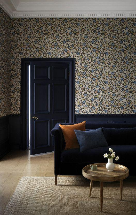 """<p>This clever use of wallpaper draws the eye upwards to the full height of the room, which is especially effective if you have interesting cornicing or feature lighting. The deep blue painted door, panelling, and matching deep blue sofa enhance this elongating effect. </p><p>Pictured: <a href=""""https://www.paintandpaperlibrary.com/catalog/product/view/id/41644/category/187/"""" rel=""""nofollow noopener"""" target=""""_blank"""" data-ylk=""""slk:Feather Flora"""" class=""""link rapid-noclick-resp"""">Feather Flora</a>, Paint & Paper Library</p>"""