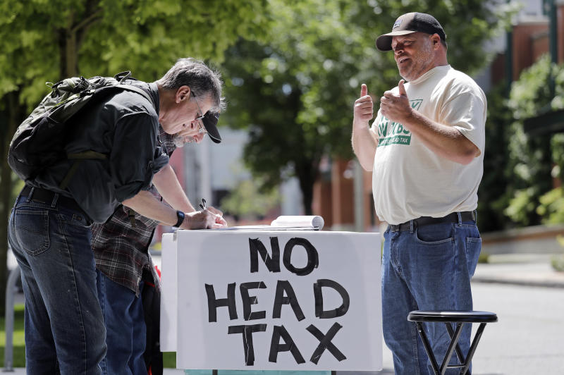 In this May 24, 2018, photo, paid signature gatherer John Ellard, right, gives thumbs-up as two men stop to sign petitions to put on the November ballot a referendum on Seattle's head tax, in Seattle. Seattle city leaders say they'll work to repeal the tax passed just last month on businesses such as Amazon and Starbucks designed to help pay for homeless services and affordable housing. Amazon and other businesses had sharply criticized the levy, and the online retail giant even temporarily halted construction planning on a new high-rise building near its Seattle headquarters in protest. (AP Photo/Elaine Thompson)