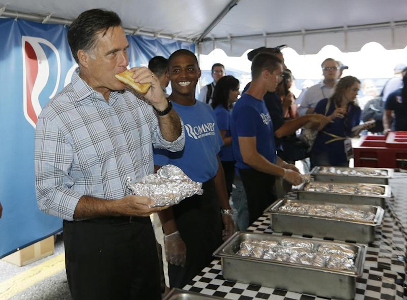 Republican presidential candidate Mitt Romney takes a bite out of a hot dog as he campaigns at the Federated Auto Parts 400 NASCAR Sprint Cup Series race at Richmond International Raceway in Richmond, Va., Saturday, Sept. 8, 2012. (AP Photo/Charles Dharapak)