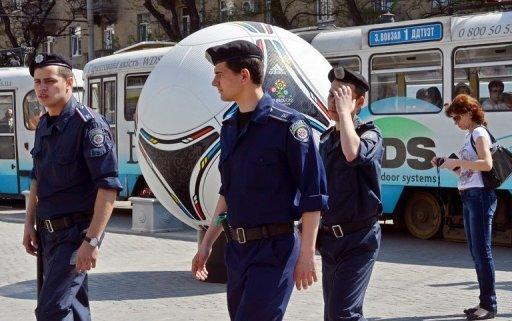 "Police officers walk past a giant model of ""Tango 12"", the official match ball of the Euro 2012 football tournament, during a patrol in Dnipropetrovsk on April 29. Four explosions went off in a busy area of central Dnipropetrovsk on Saturday, wounding 26"