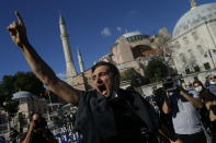 People chant slogans following Turkey's Council of State's decision, outside the Byzantine-era Hagia Sophia, one of Istanbul's main tourist attractions in the historic Sultanahmet district of Istanbul, Friday, July 10, 2020.Turkey's Council of State, threw its weight behind a petition brought by a religious group and annulled a 1934 cabinet decision that changed the 6th century building into a museum. The ruling allows the government to restore the Hagia Sophia's previous status as a mosque.The decision was in line with the Turkish President's Recep Tayyip Erdogan's calls to turn the hugely symbolic world heritage site into a mosque despite widespread international criticism, including from the United States and Orthodox Christian leaders. (AP Photo/Emrah Gurel)