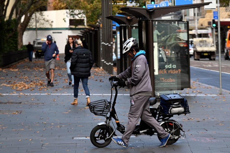 A courier crosses the road to deliver food in the central business district in Sydney on May 14, 2020. - Almost 600,000 Australians lost their jobs as the virus shutdown took hold in April, the steepest monthly drop since records began more than 40 years ago, data showed on May 14. (Photo by Saeed KHAN / AFP) (Photo by SAEED KHAN/AFP via Getty Images)