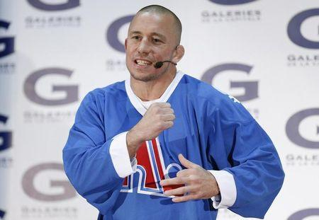 FILE PHOTO: Georges St-Pierre gestures as he speaks during a news conference at Les Galeries de la Capitale shopping centre in Quebec City, December 13, 2013. REUTERS/Mathieu Belanger