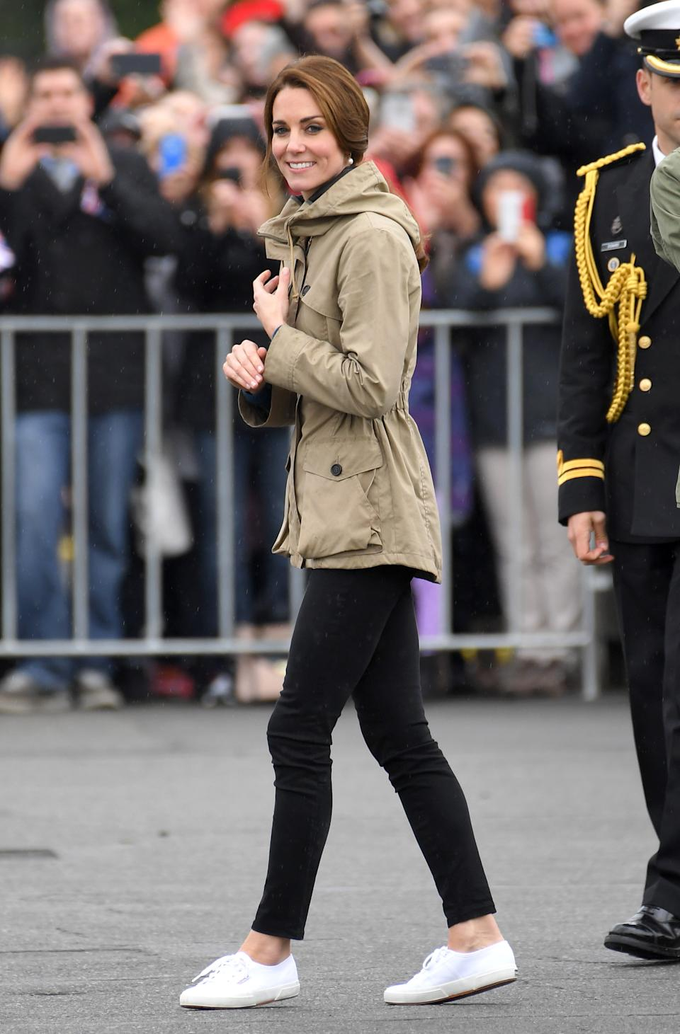 kate middleton wearing white superga sneakers, black skinny jeans, and a tan coloured jacket at an event