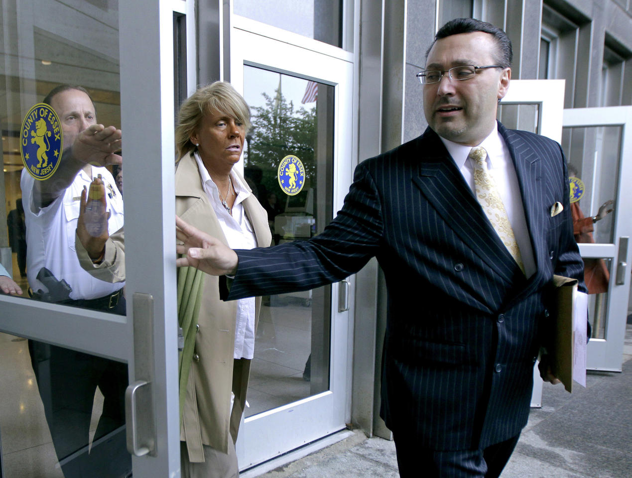 Patricia Krentcil, 44, center, walks out of Essex County Superior Court with her lawyer John Caruso, right, after court appearance on charges of child endangerment, Wednesday, May 2, 2012 in Newark, N.J. Krentcil is accused of taking her 5-year-old child into a tanning booth. Krentcil tells The Associated Press her daughter got her sunburn from being outside on a recent warm day. New Jersey state law prohibits anyone under 14 from using tanning salons.(AP Photo/Julio Cortez)