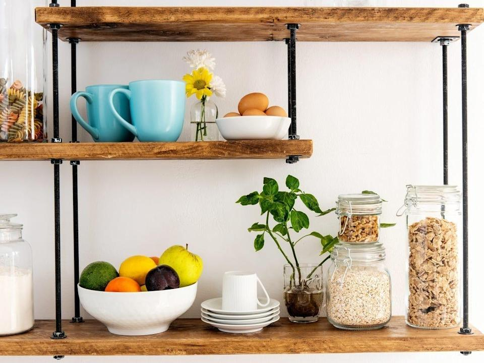 Kitchen shelves with fruit, colorful mugs, flowers, and plants.