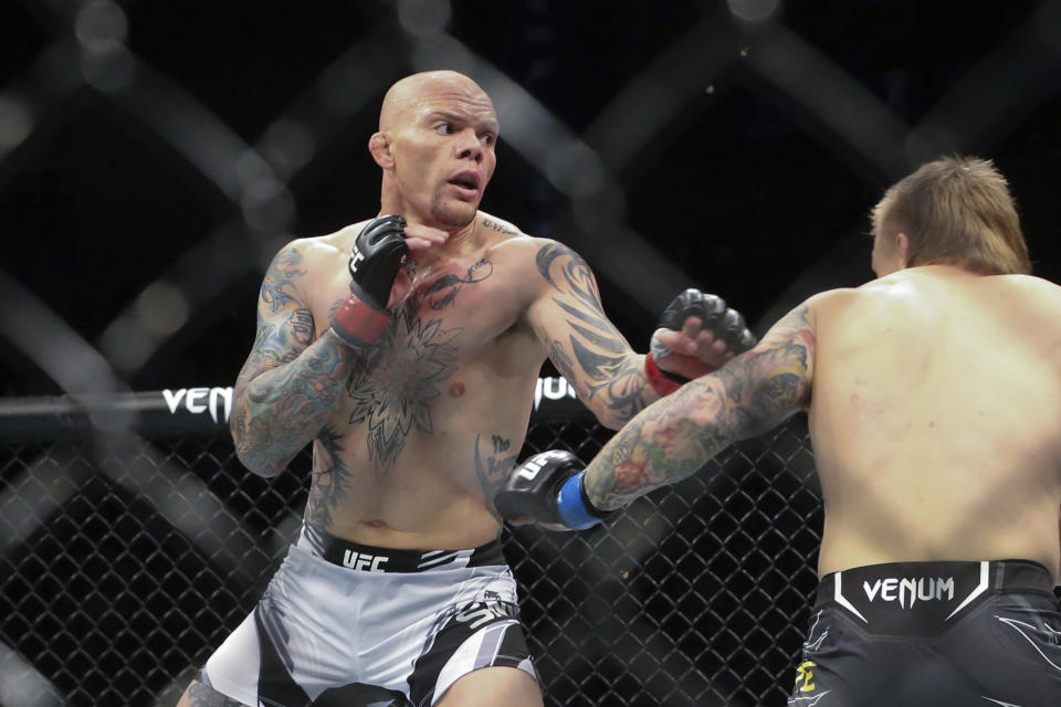 Anthony Smith, left, looks for an opening to hit Jimmy Crute during a UFC 261 mixed martial arts bout, Saturday, April 24, 2021, in Jacksonville, Fla. It is the first UFC event since the onset of the COVID-19 pandemic to feature a full crowd in attendance. (AP Photo/Gary McCullough)