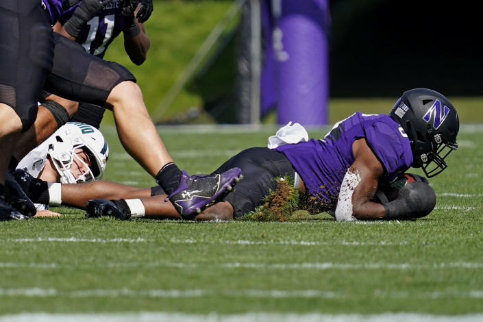 Northwestern defensive back Coco Azema, right, recovers a fumble by Ohio quarterback Kurtis Rourke, left, during the first half of an NCAA college football game in Evanston, Ill., Saturday, Sept. 25, 2021. (AP Photo/Nam Y. Huh)