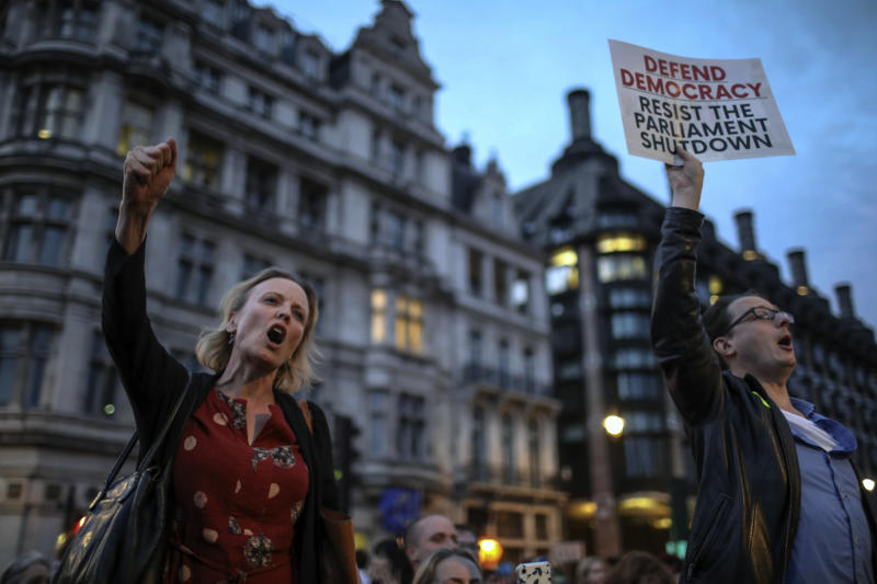 Anti-Brexit supporters take part in a protest in front of the Houses of Parliament in central London, Wednesday, Aug. 28, 2019. British Prime Minister Boris Johnson maneuvered on Wednesday to give his political opponents even less time to block a no-deal Brexit before the Oct. 31 withdrawal deadline, winning Queen Elizabeth II's approval to suspend Parliament. (AP Photo/Vudi Xhymshiti)