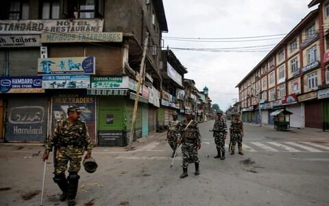 <span>Indian security forces patrol a deserted street in Srinagar during restrictions after the government scrapped special status for Kashmir</span> <span>Credit: DANISH ISMAIL/ REUTERS </span>