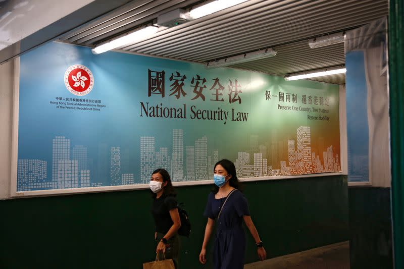 FILE PHOTO: Women walk past a government-sponsored advertisement promoting the new national security law as a meeting on national security legislation takes place in in Hong Kong