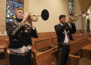 Los Changuitos Feos (Ugly Little Monkeys) Mariachi band members Cameron Davison 18, and Roman Murillo 14, play their trumpets as they preform during the morning Mass at St. Augustine Cathedral Sunday, Aug. 18, 2021 in downtown Tucson. (AP Photo/Darryl Webb)